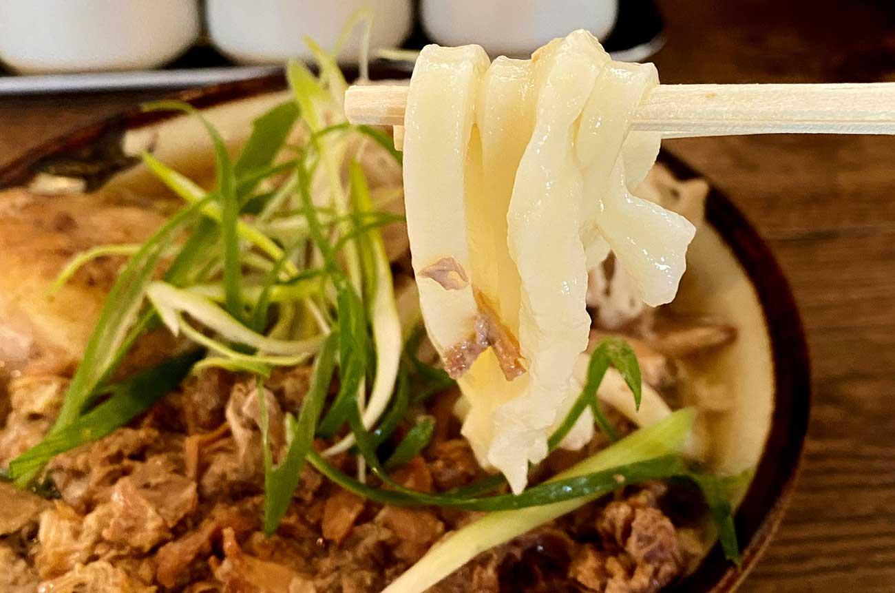 肉29うどんの麺を持ち上げる